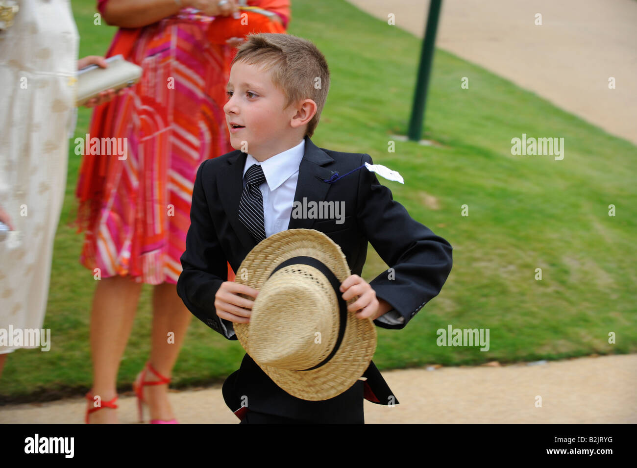 Glorious Goodwood ladies day -  a young boy running holding his straw boater. - Stock Image