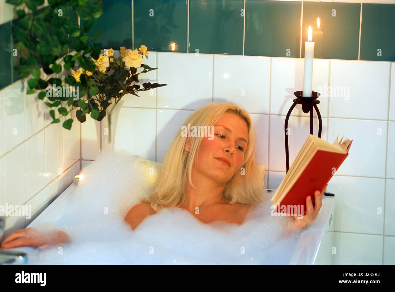Woman reading book in warm candle lit bubble bath Stock Photo ...