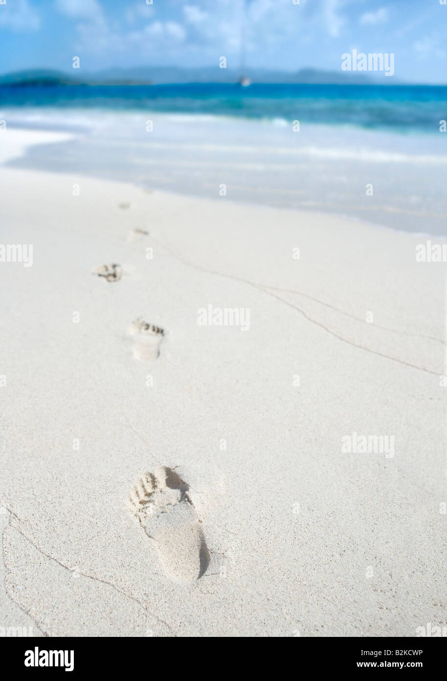 Footprints on a sunny tropical beach in the Caribbean - Stock Image