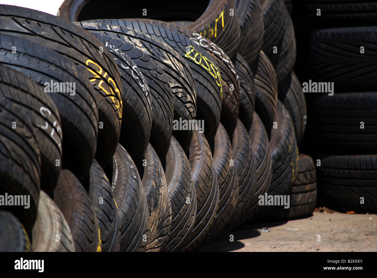 Tyres stacked for recycling - Stock Image