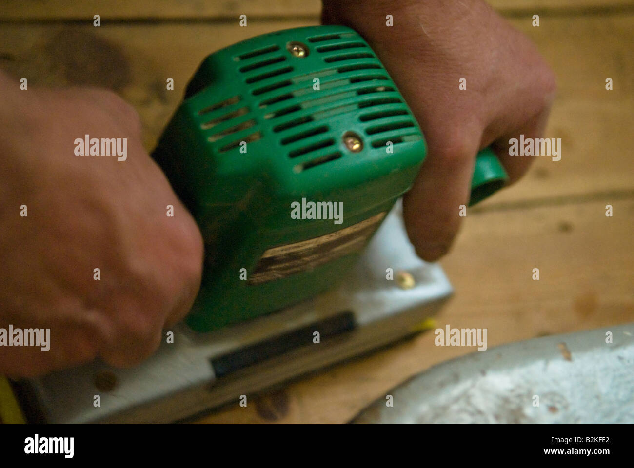 Sanding wooden boards with an orbital sander - Stock Image