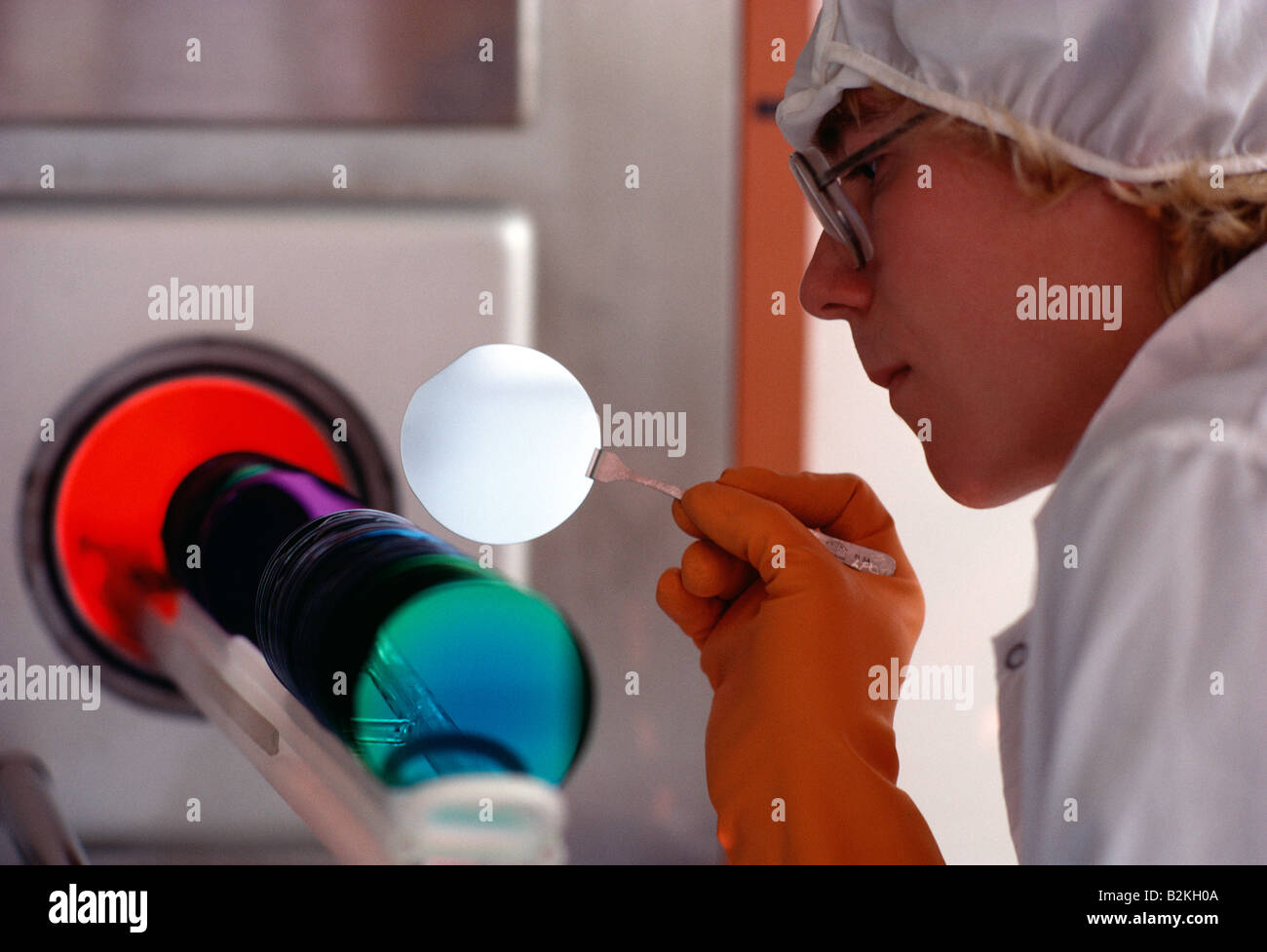 Technician places silicon wafer into a special rack in preparation for baking in the manufacturing of computer chips - Stock Image