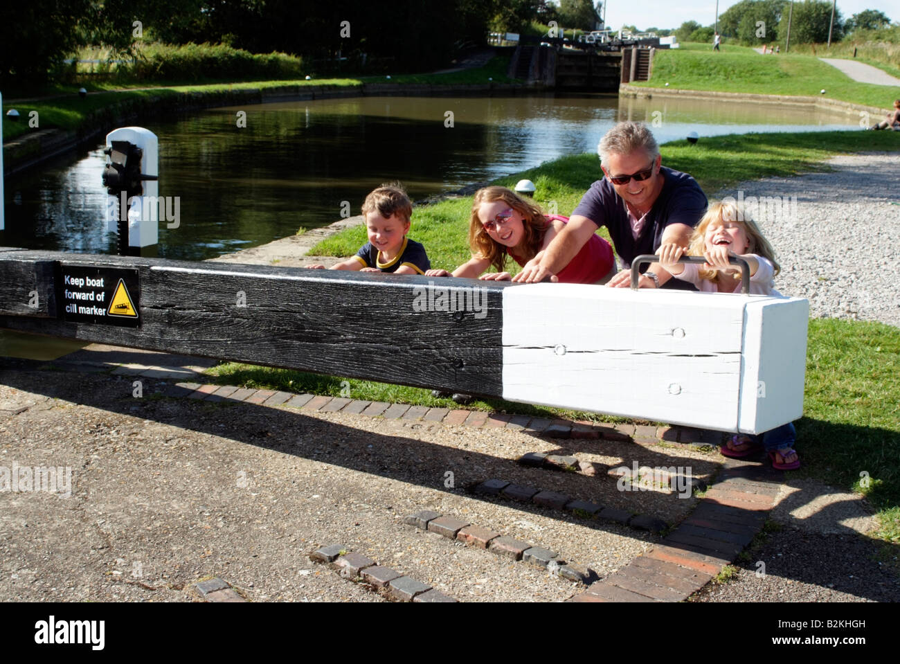 Children on a boating holiday push open lock gate Grand Union Canal England with the help of their father - Stock Image
