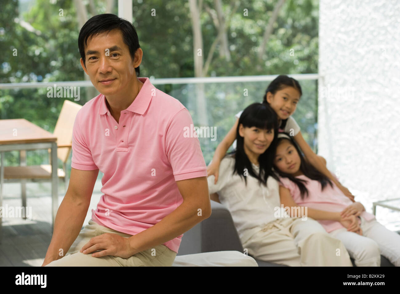 Portrait of a mid adult man smiling with his family in the background in a living room Stock Photo