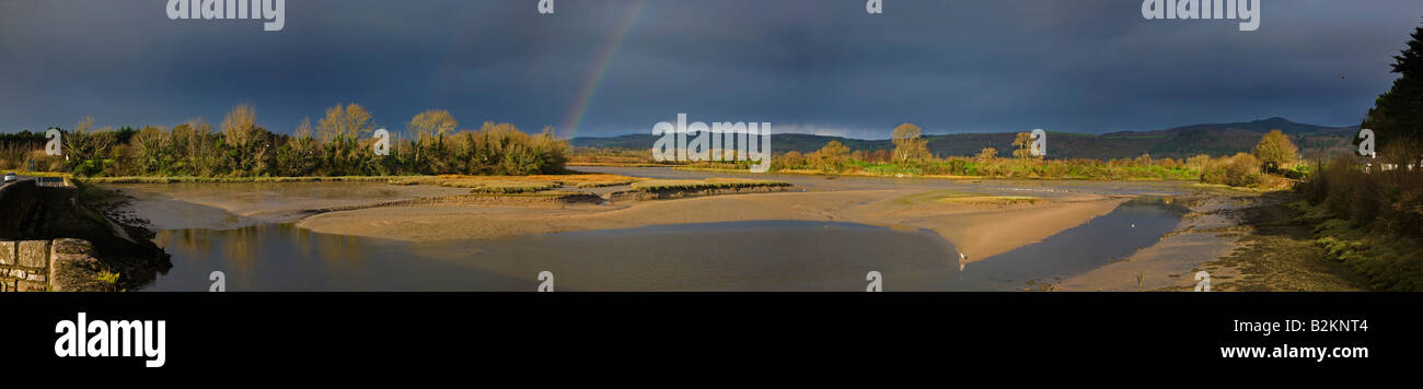 Dark stormy clouds and rainbow over the bird reserve at Barnawee, Dungarvan, County Waterford, Ireland - Stock Image