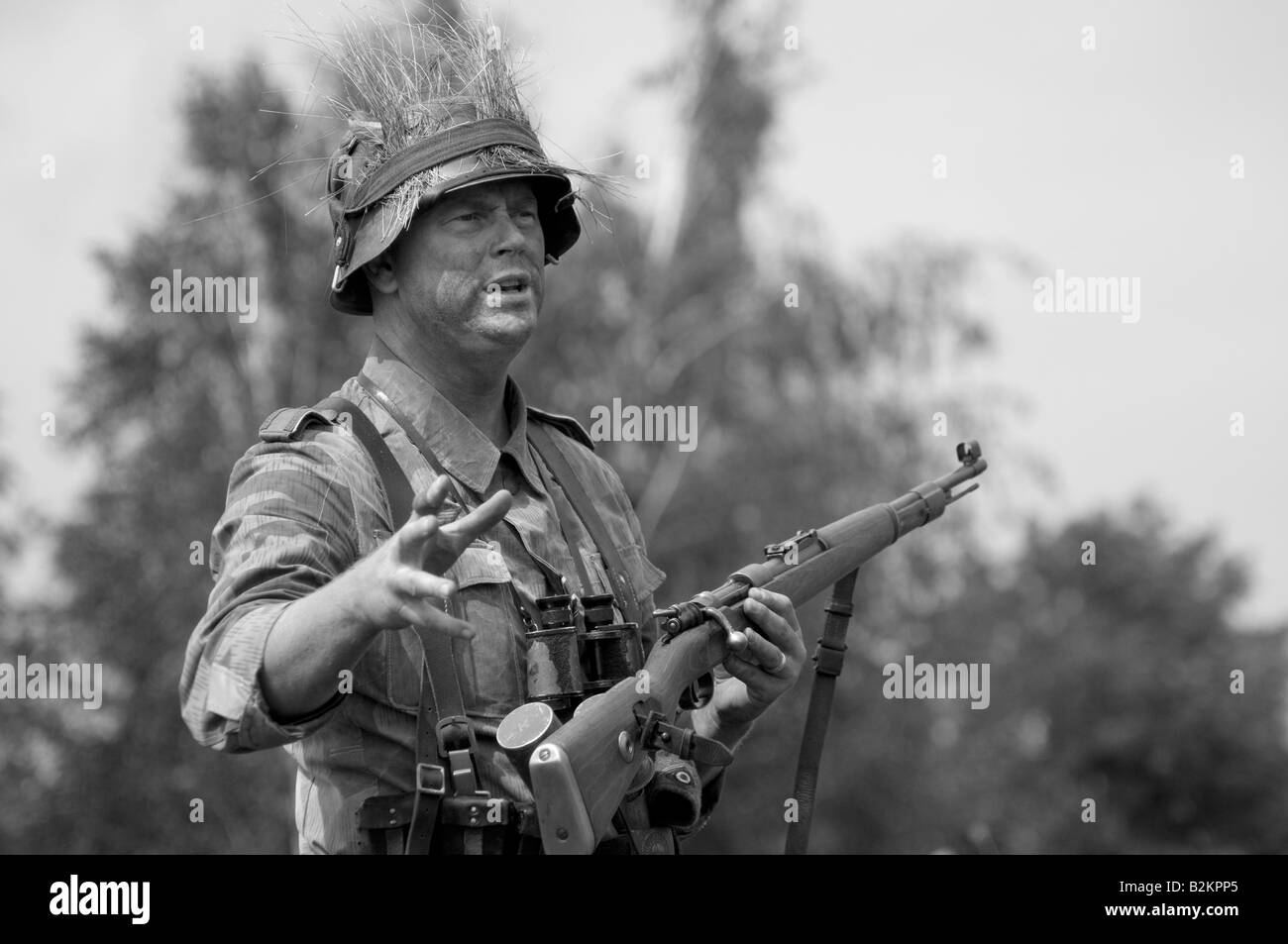 A German army Unteroffizier giving ad hoc training for field tactics to new troops - Stock Image