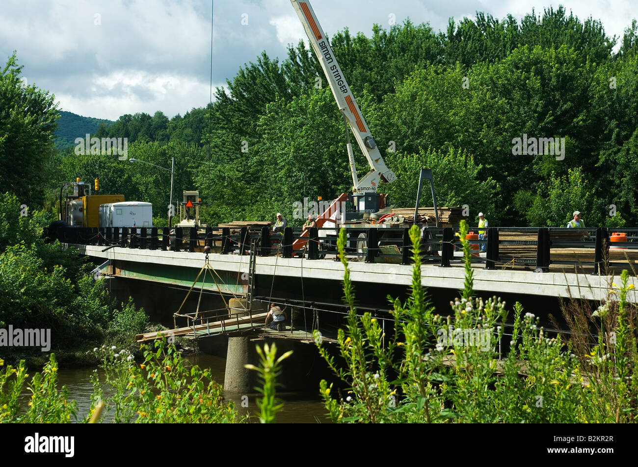Bridge repair crew working on Wrong Way Bridge over the LaMoille River in Cambridge, VT US after recent flooding - Stock Image