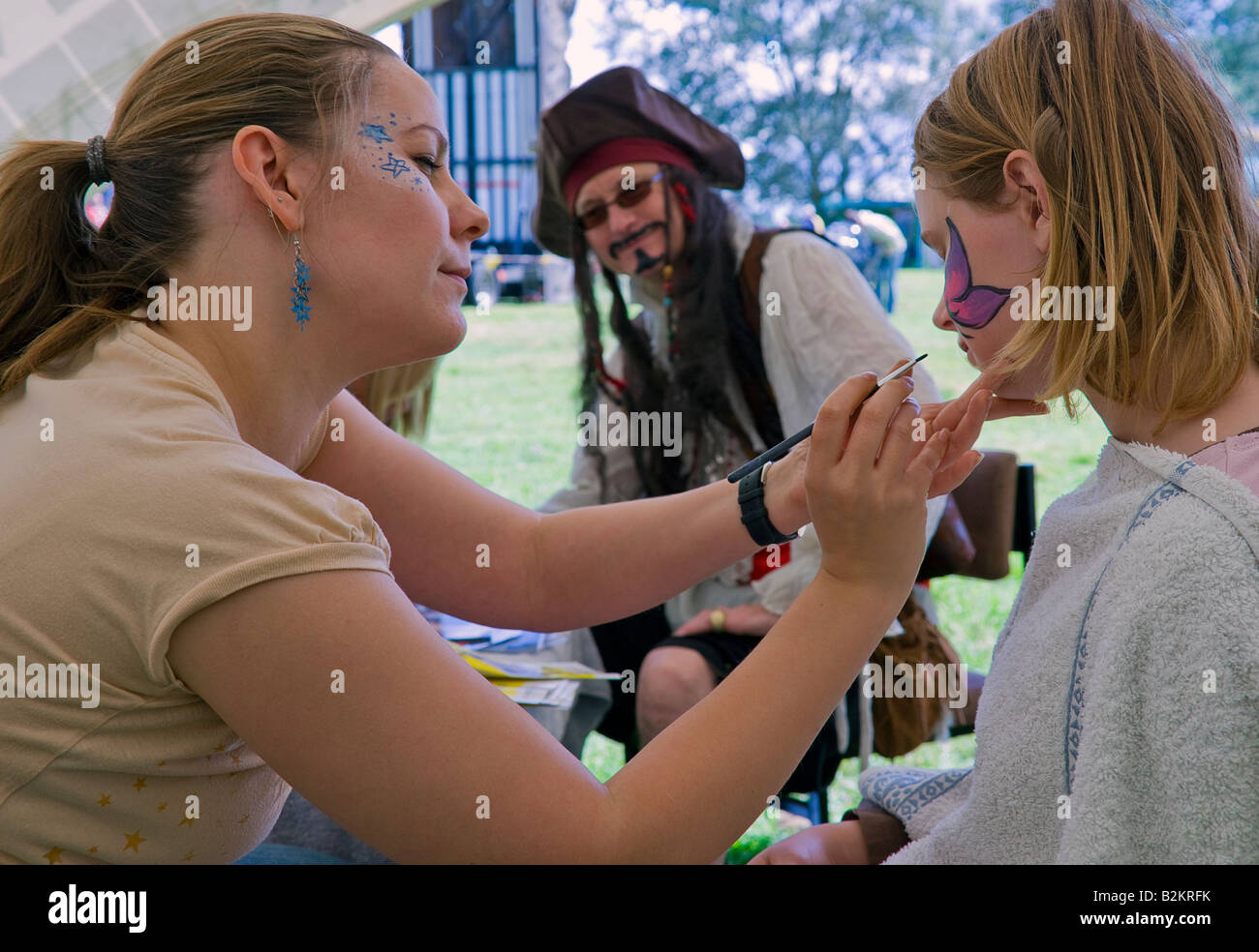 Young girl having her face painted at an activity stall at a riverside gala - Stock Image