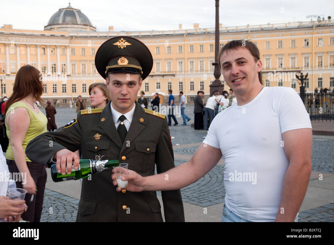 Policeman pouring glass of fizzy wine on Dvortsovaya Ploshchad on one of the White Nights St Petersburg Russia - Stock Image