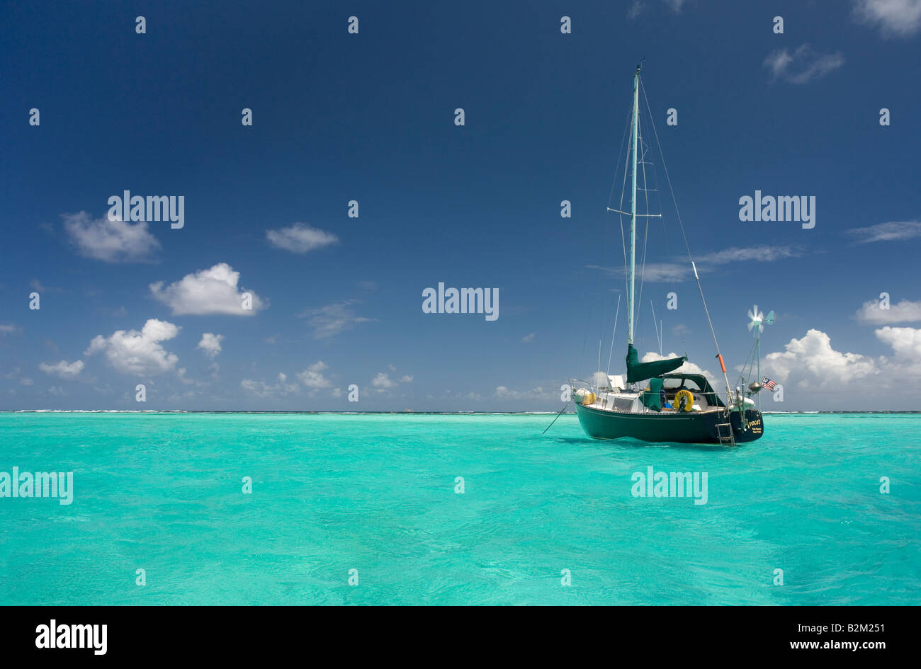 A lone cruising sailboat on the Caribbean This one was at teh Tobago Cays just inside Horseshoe Reef - Stock Image