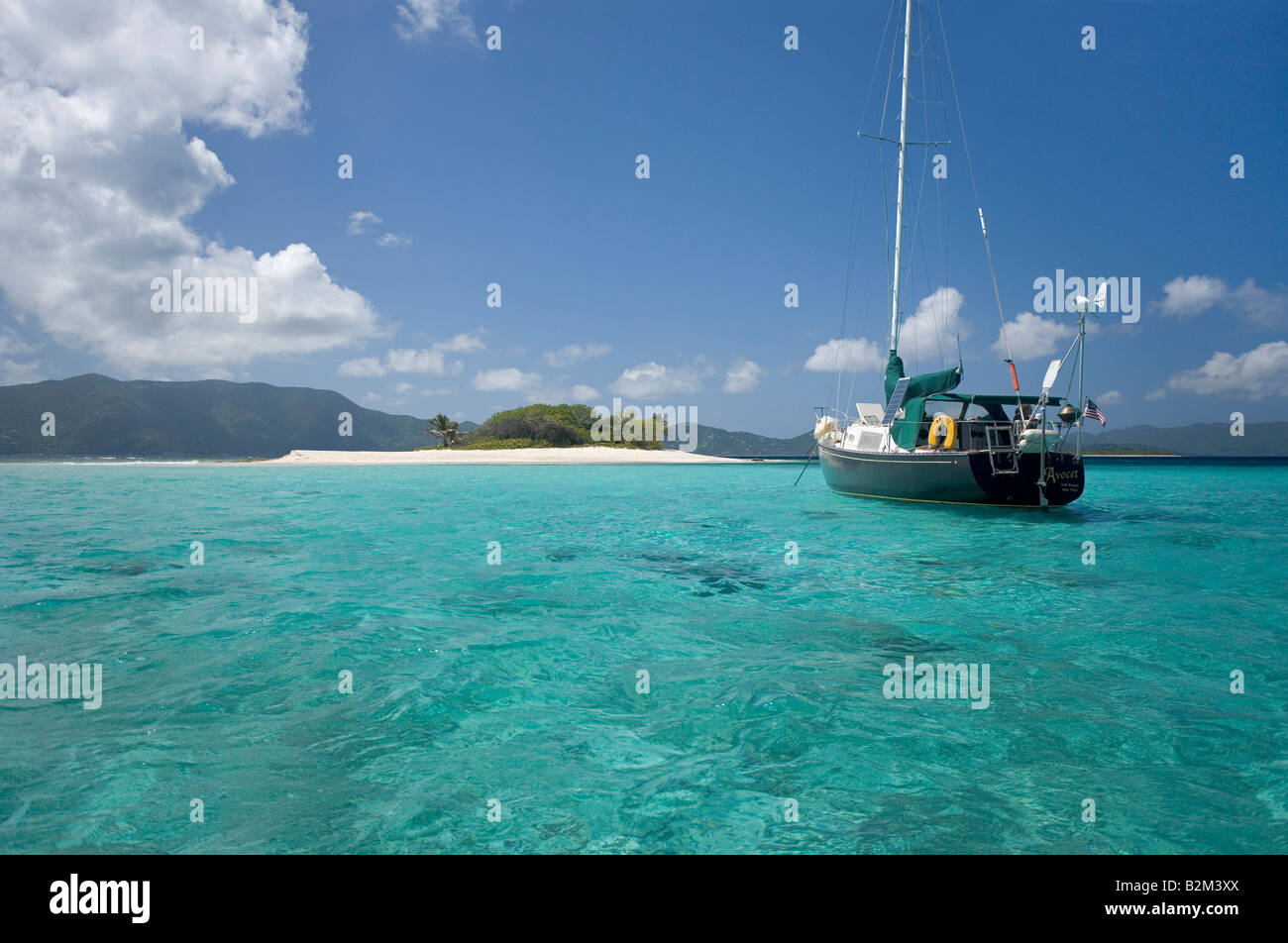 A cruising sailboat anchored at Sandy Spit Island in the British West Indies - Stock Image