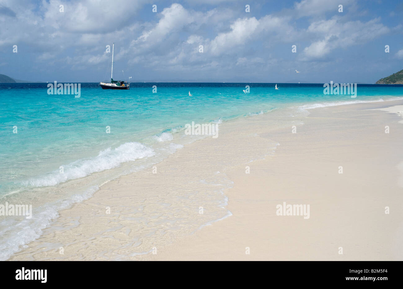 A cruising sailboat anchored next to Sandy Cay in the British Virgin Islands Looking east St Thomas is visible in - Stock Image