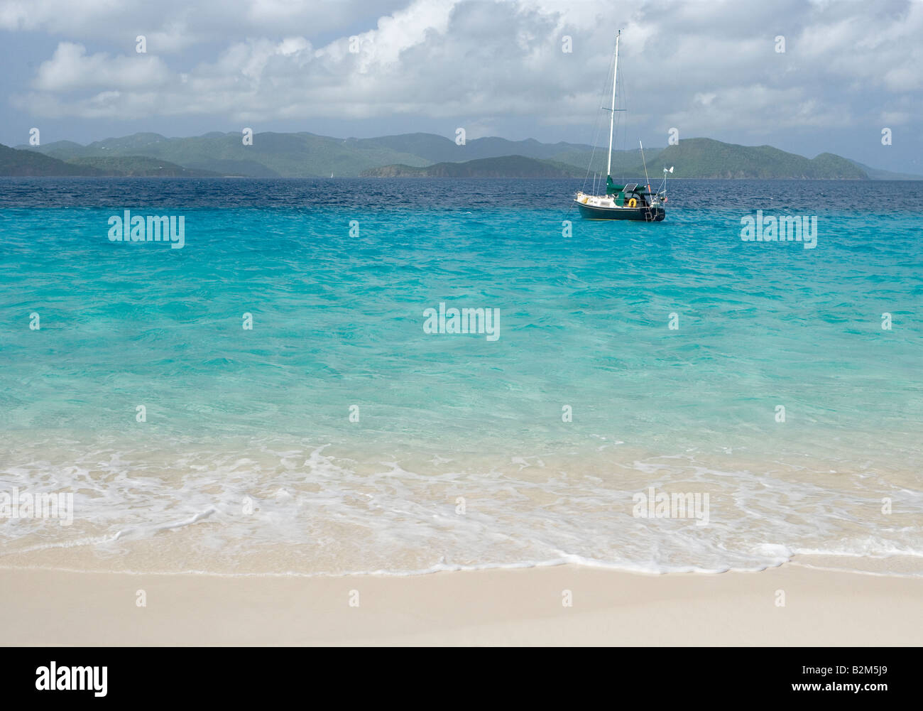 A cruising sailboat anchored next to Sandy Cay in the British Virgin Islands St John is visible in the background - Stock Image