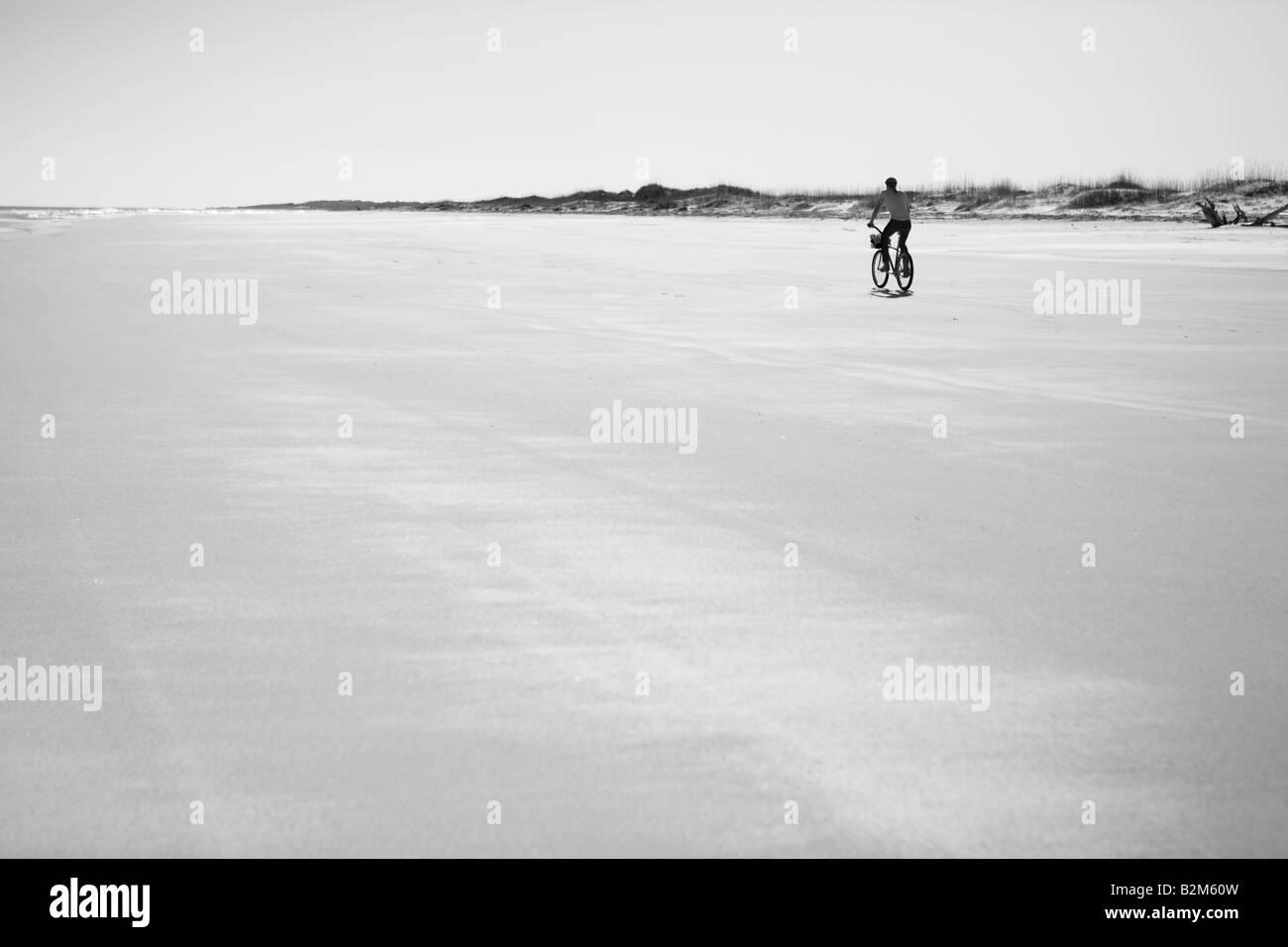 MAN RIDING A BICYCLE ON THE BEACH ON CUMBERLAND ISLAND GEORGIA USA - Stock Image