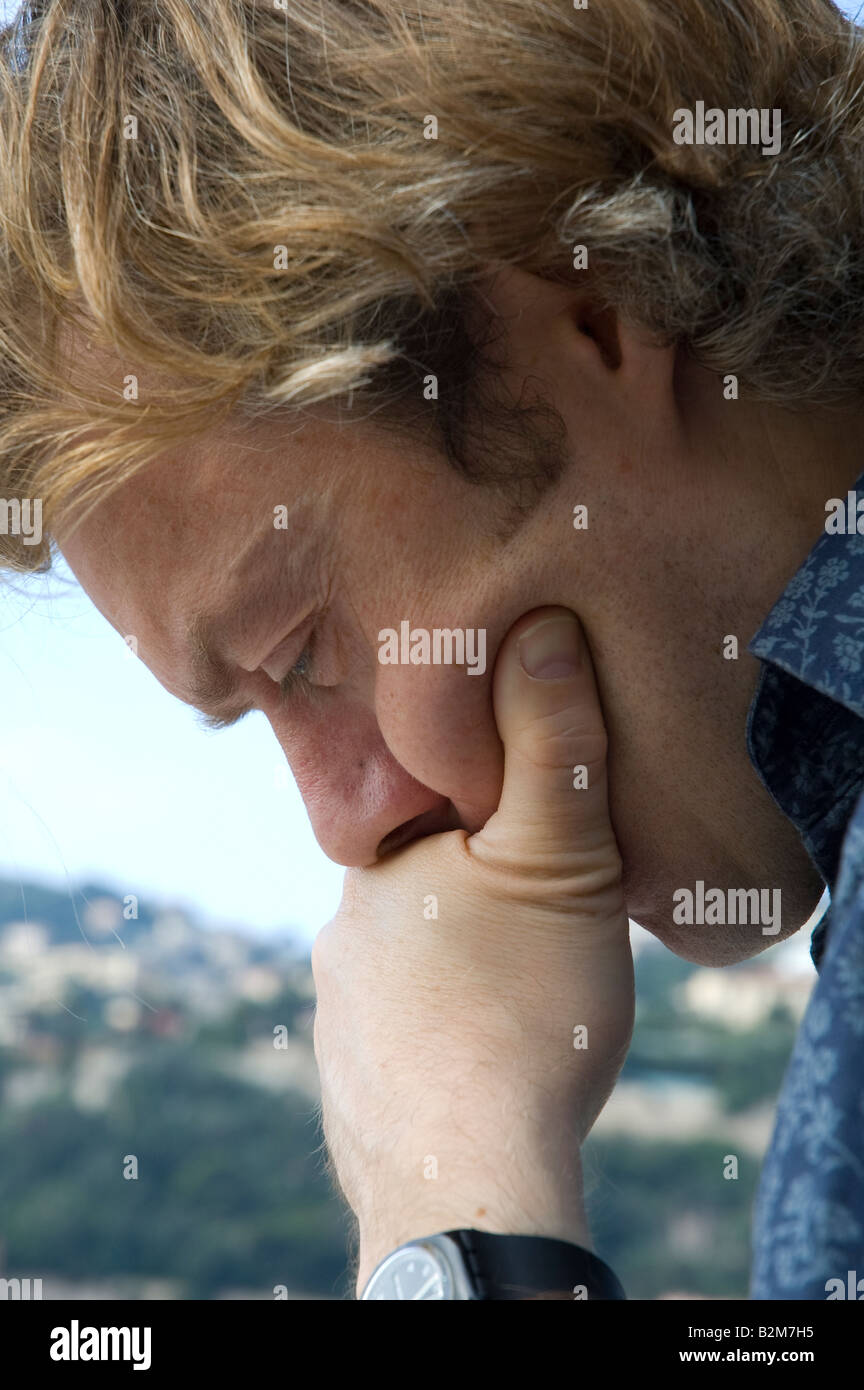man thinking alone outside with hand resting on chin Stock Photo