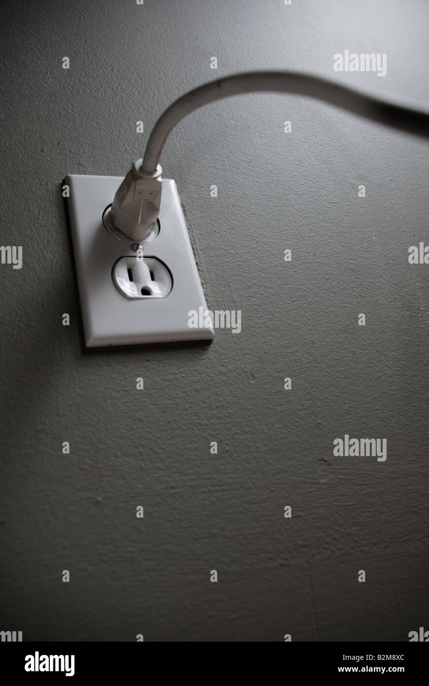 Looking up to and acasting a dark shadow a long white cord plugged into a white power outlet against a grey painted - Stock Image