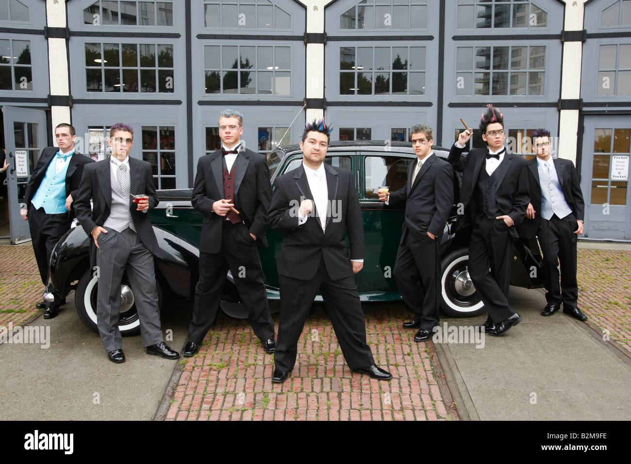 men in tuxedos posing in front of an old car - Stock Image