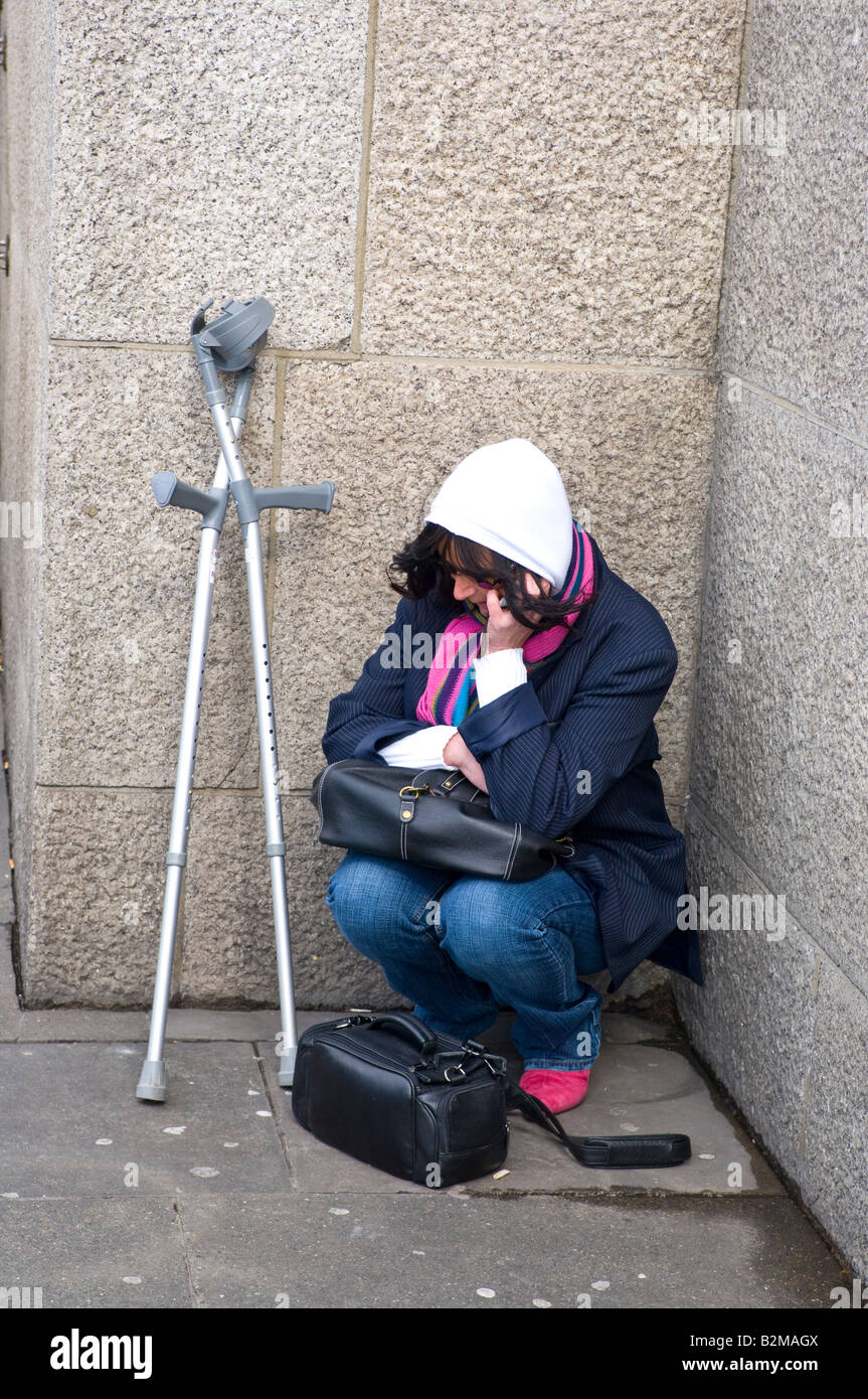 A woman in her 30s on a cell phone crouched in the corner on the street a pair of crutches nearby. - Stock Image