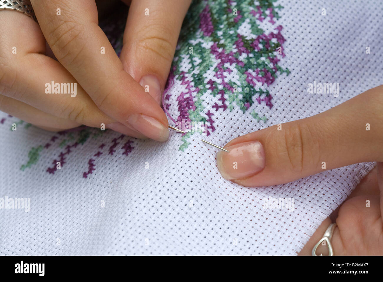 Fingers of young women cross embroidery - Stock Image
