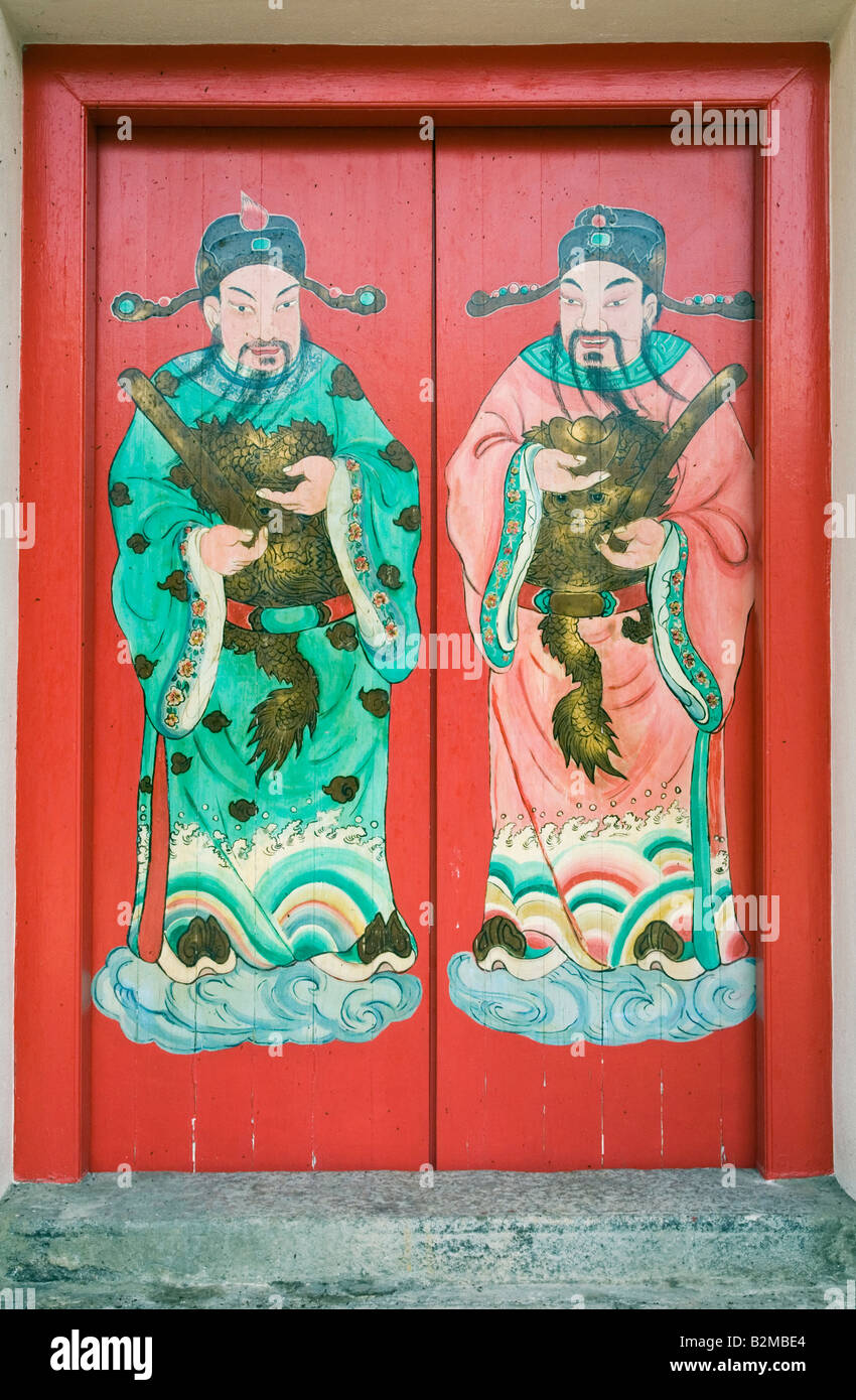 Double red wooden doors with artistic god figures at the ancestral straits Chinese clan temple, Cheah Si Sek Tek - Stock Image