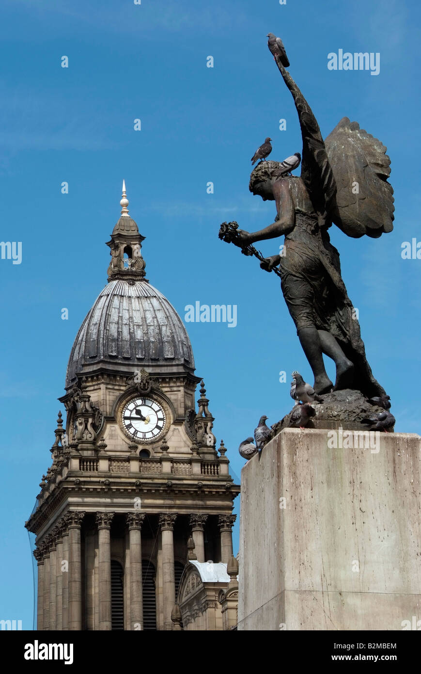 Leeds town hall clock tower seen beyond the war memorial angel sculpture - Stock Image