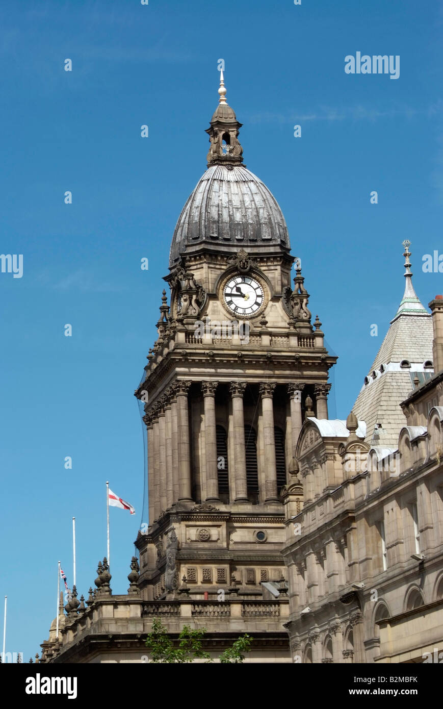 Leeds town hall clock tower seen beyond the roofline of the library building - Stock Image