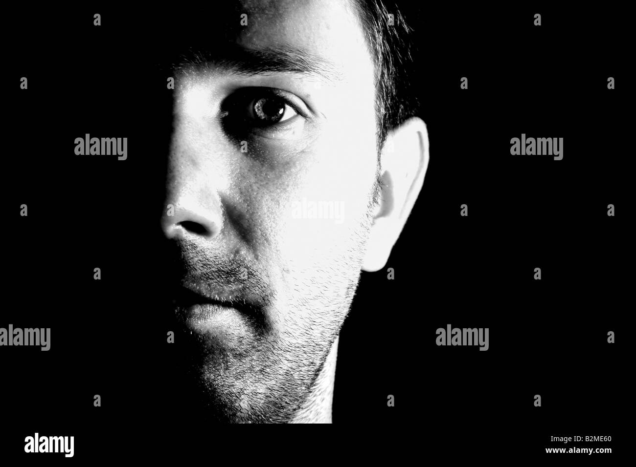 A stark black and white portrait of a caucasian man's face, half in shadow - Stock Image