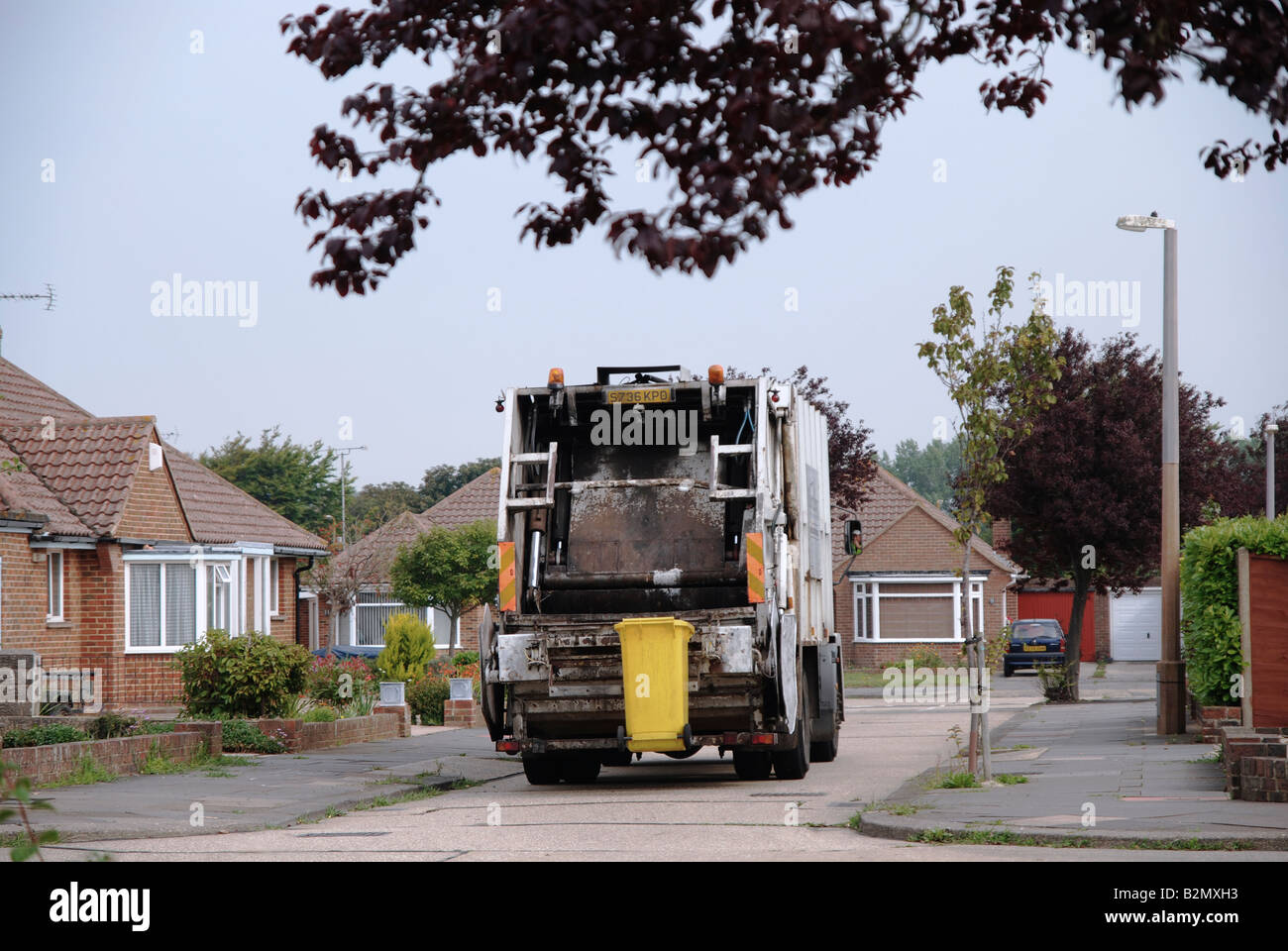 dustcart collecting rubbish for landfill Worthing Adur area West Sussex reversing down a residential close - Stock Image