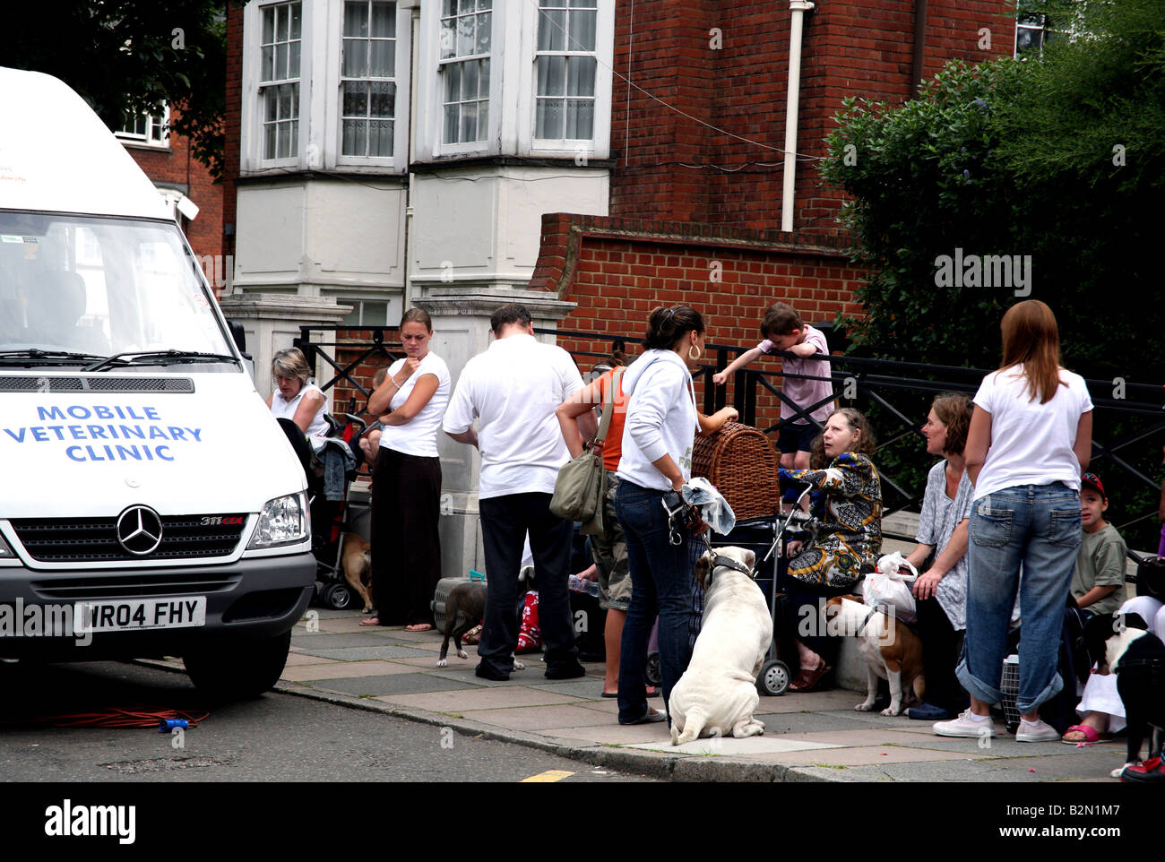 People & pets wait for mobile vets clinic in London - Stock Image