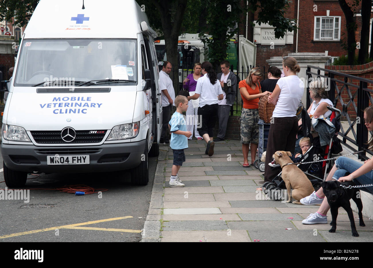 People & their pets wait for mobile vets van, London - Stock Image