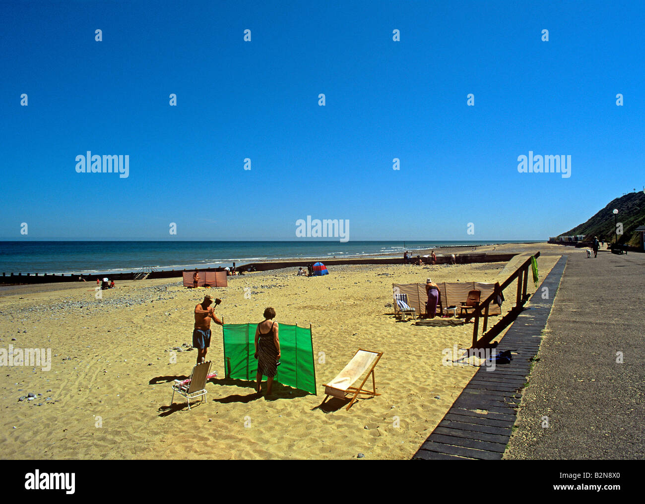 Cromer beach on a windy day with visitors erecting windbreaks to protect from winds off the North Sea Norfolk - Stock Image