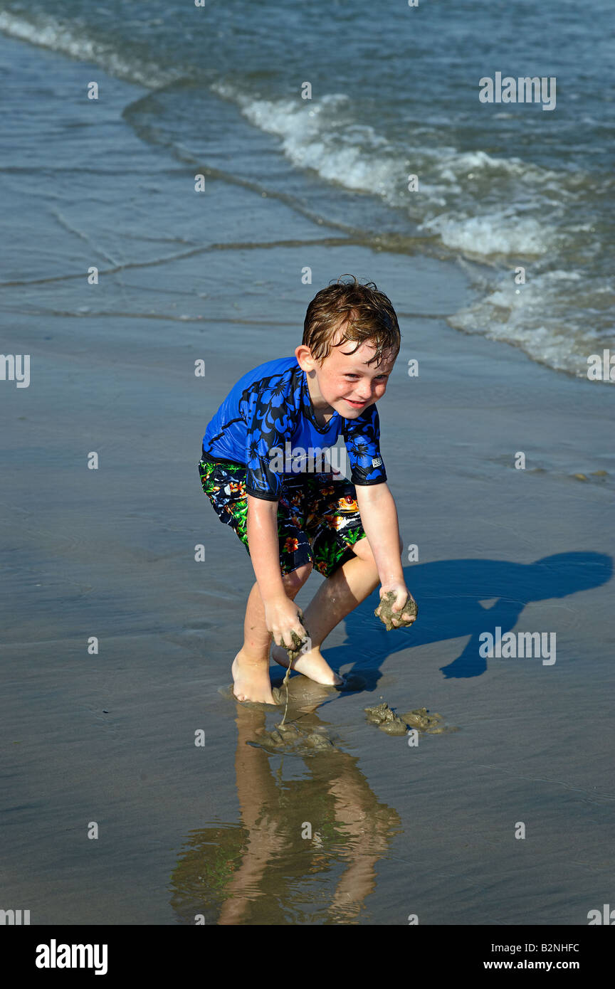 Boy plays with sand at the waters edge Ocean City, New Jersey, USA - Stock Image