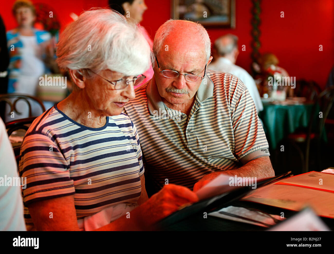 Senior couple reviewing a restaurant menu - Stock Image