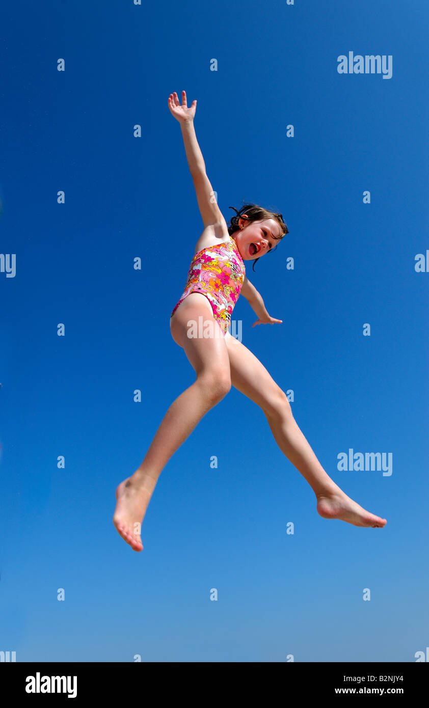 Joyful girl jumping. - Stock Image
