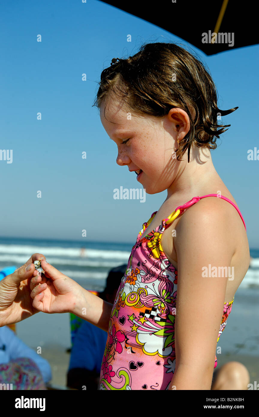 Young girl proudly displays a seashell found along the beach - Stock Image