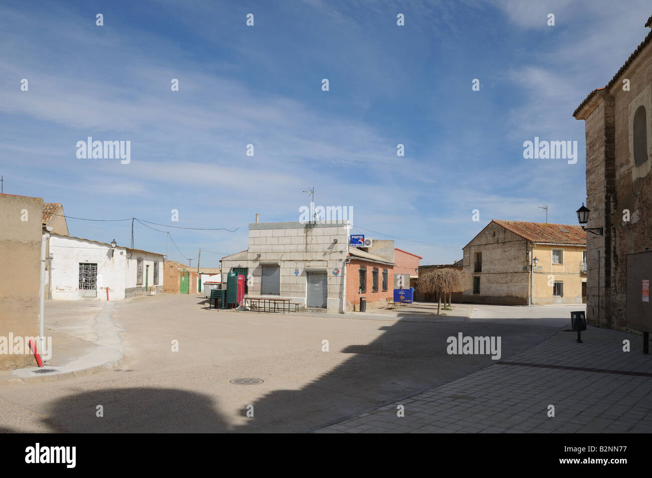 Deserted square of cheap tawdry modern buildings including shuttered closed shop and bar in village of Banos de - Stock Image