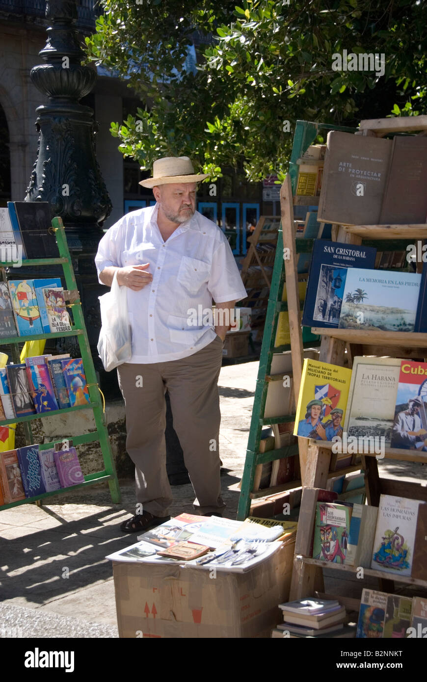 Man browsing second hand books for sale at a book market on Plaza De Armas in La Habana Vieja Havana Cuba - Stock Image