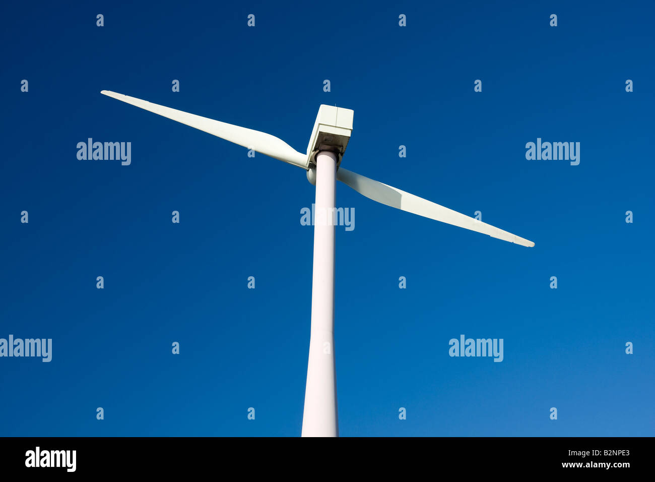 Two Bladed Windmill Against a Blue Sky - Stock Image