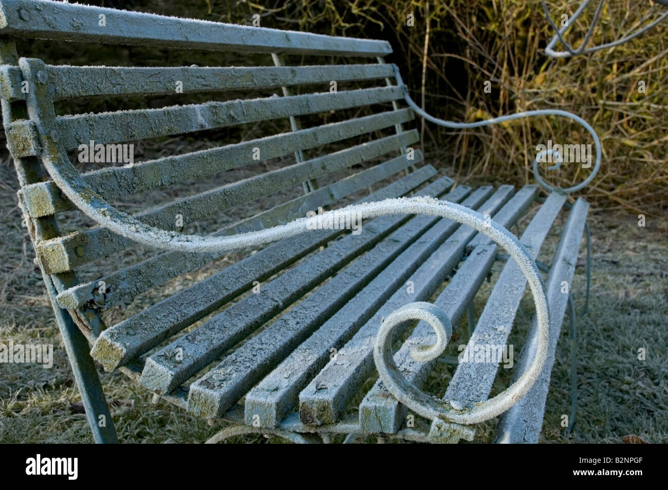 Garden bench covered in hoar frost in Winter Stock Photo