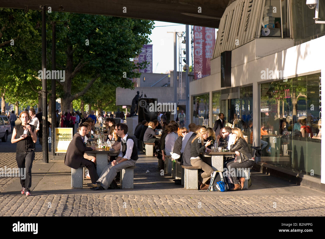 People enjoy drink outside British Film Institute on warm summer afternoon Southbank SE1 London United Kingdom - Stock Image