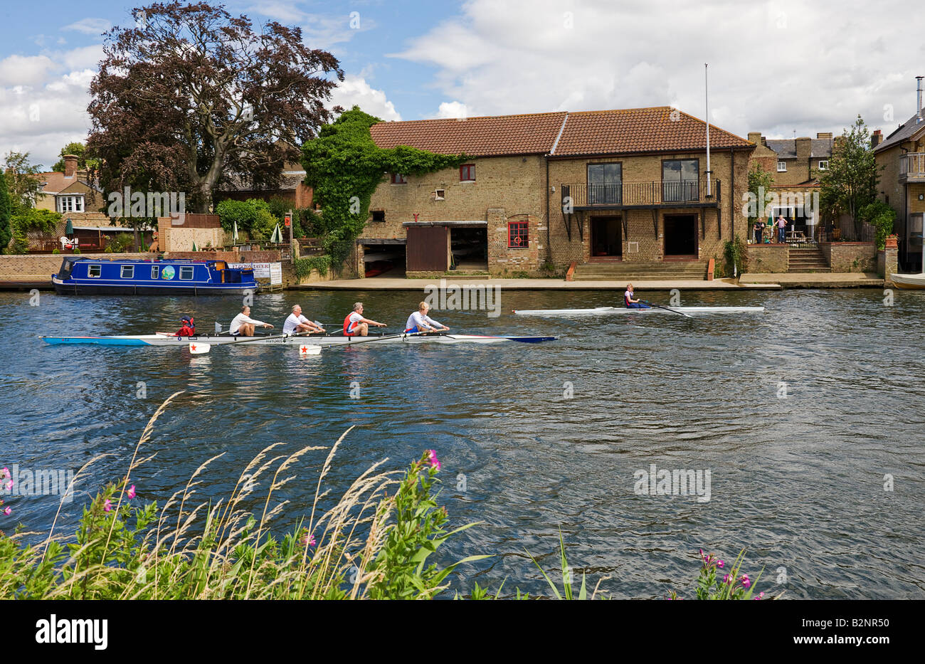 A four seater racing shell passing the rowing club boat house making for the starting line on the River Ouse. - Stock Image