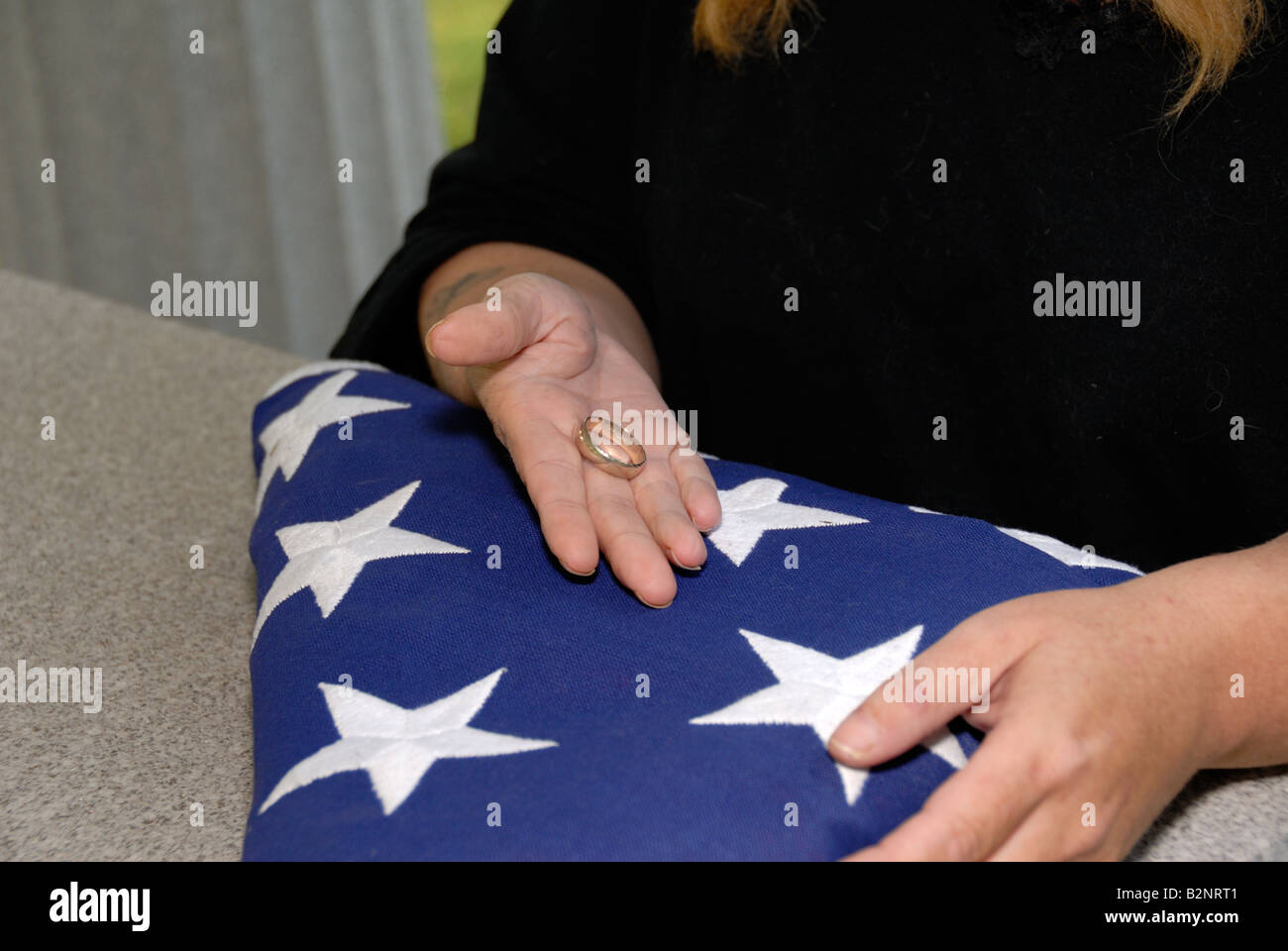 Woman Holding Husbands Wedding Ring With Folded American Flag On Granite  War Tomb Memorial   Stock