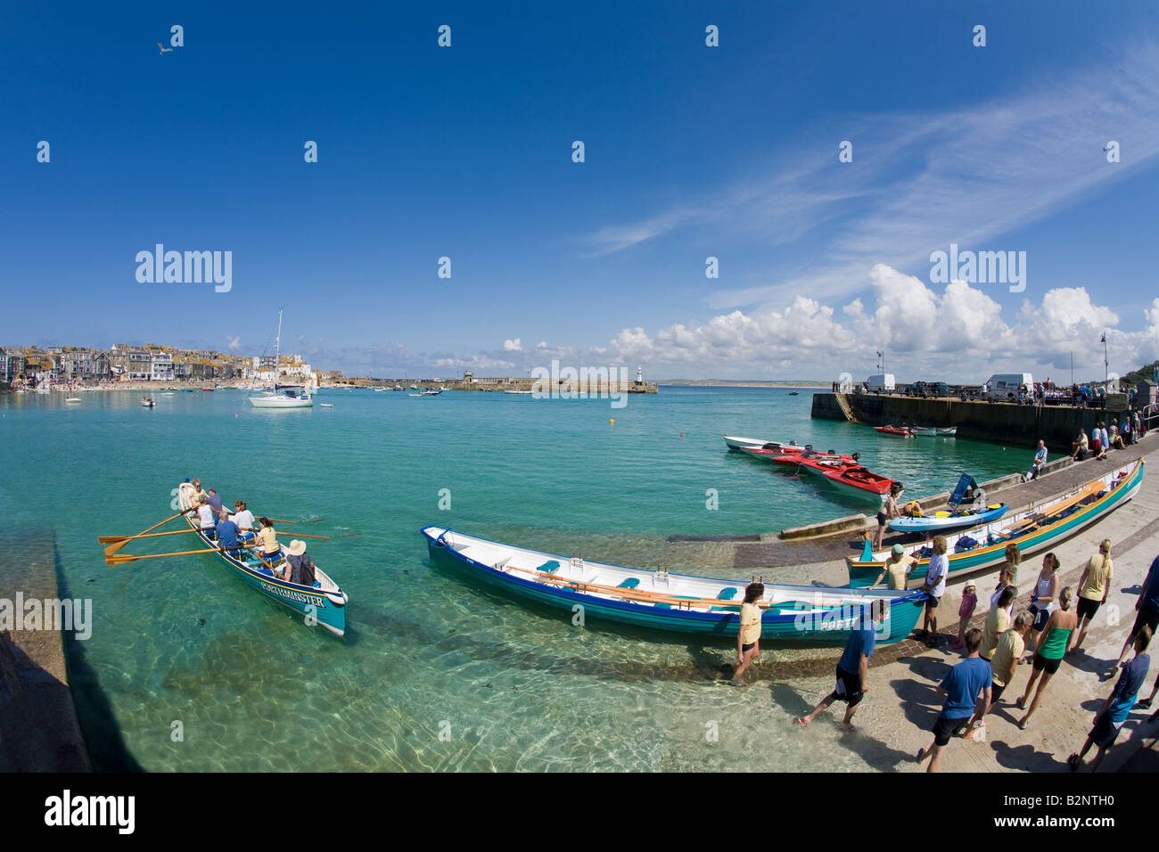 Youngsters rowing a cornish pilot gig in the old harbour harbor in summer sunshine St Ives Cornwall West Country - Stock Image