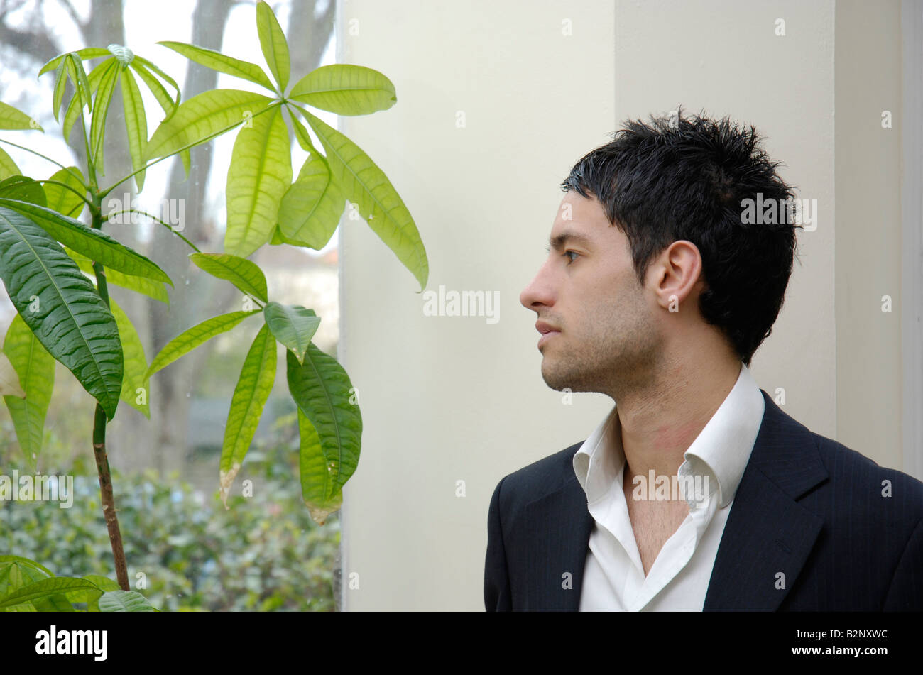 A young business man looking out of the window contemplating environmental issues, ESG investing and sustainable business models concept. Stock Photo