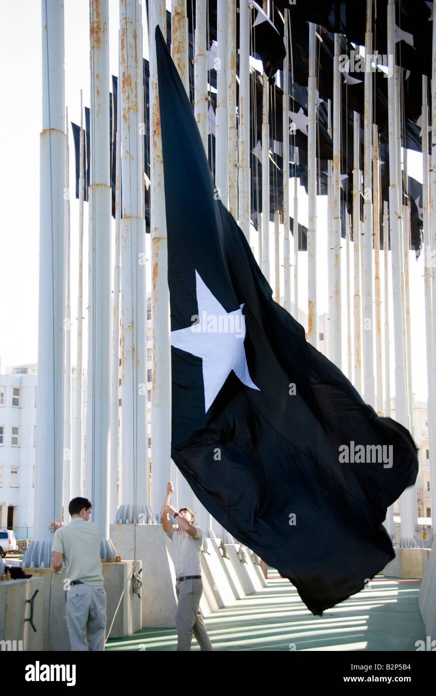 Cubans raising flag at the Mount of Flags memorial at the Jose Mart Anti Imperialist Plaza Havana Cuba - Stock Image