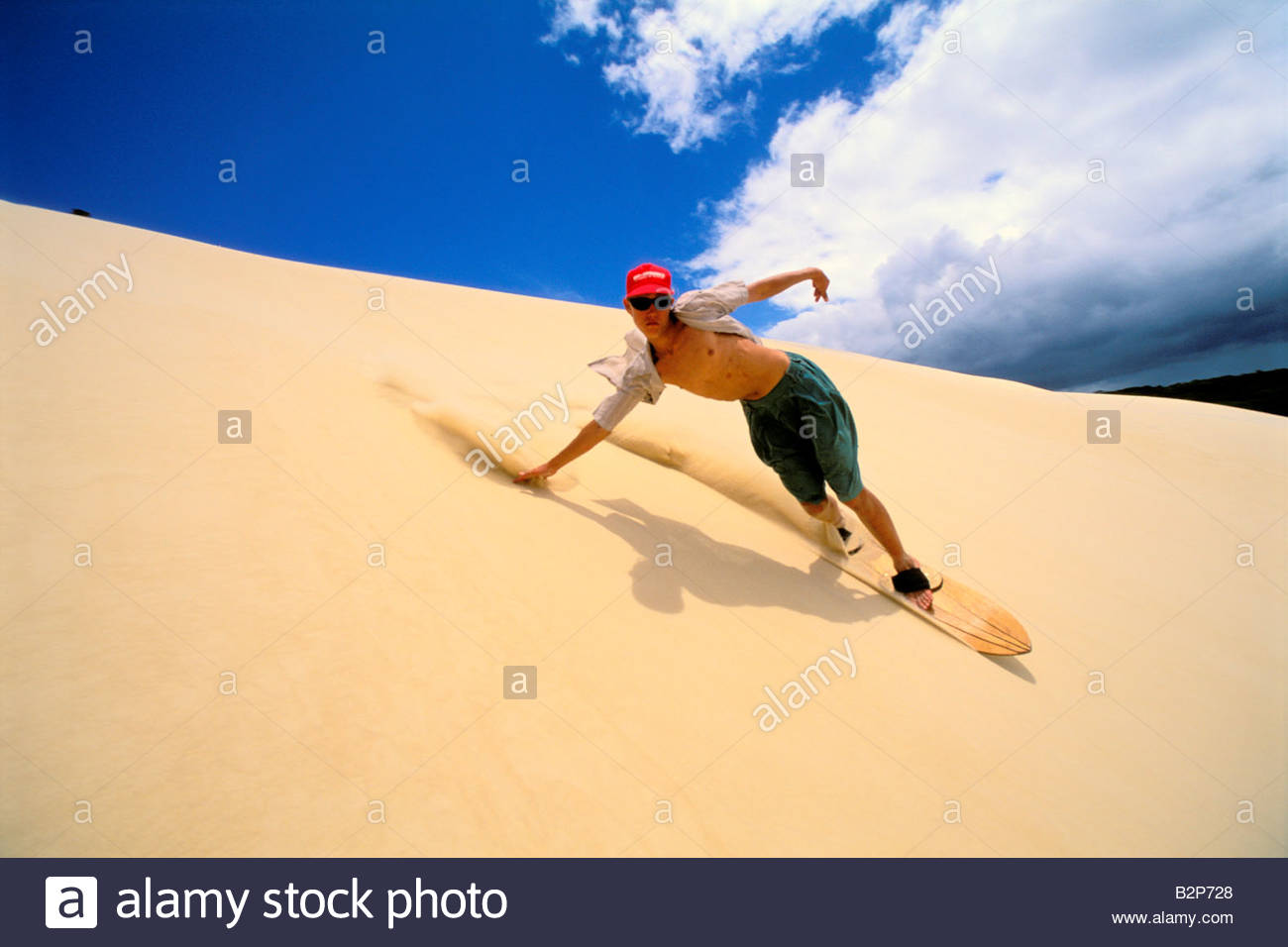 Young Man Surfing Down A Sand Dune With A Sandboard On