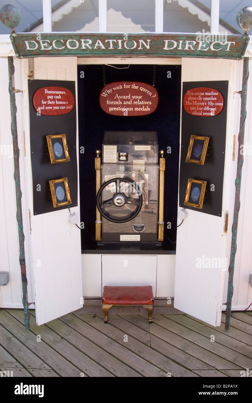 Coin mangling machine on Southwold Pier which presses a stamp onto a flattened penny coin - Stock Image