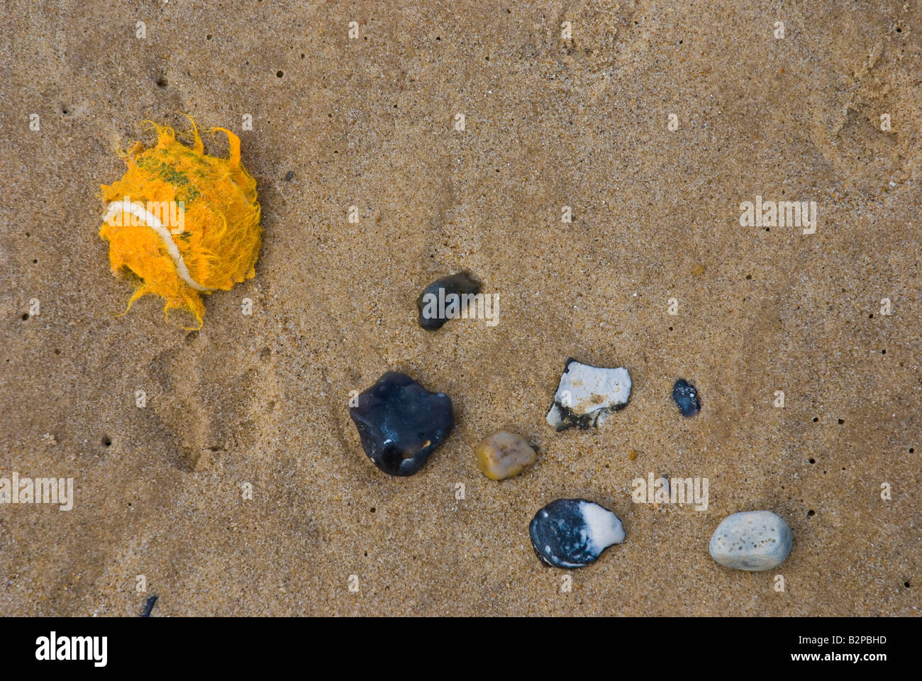 Orange tennis ball washed up on beach with pebbles - Stock Image