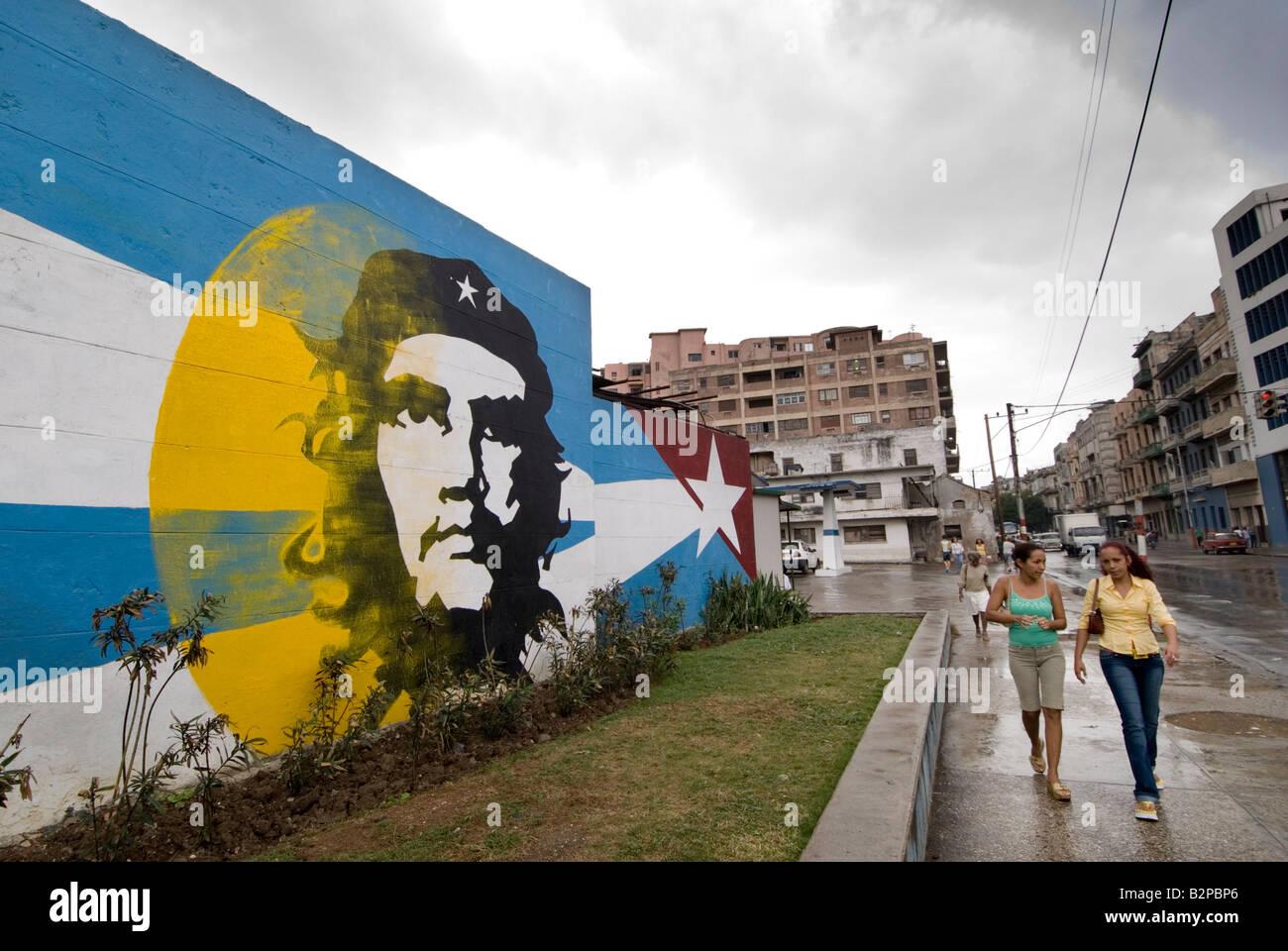 Cuban women walking past Ernesto Che Guevara mural. Centro. Havana. Cuba - Stock Image