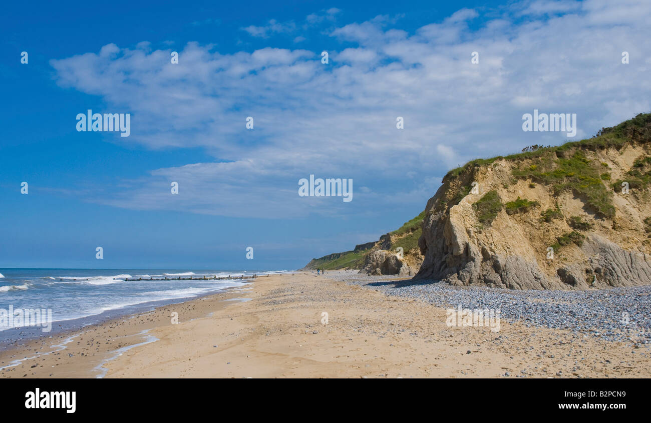 cliffs pebbly beach and sea on a sunny summer's day at Overstrand beach Cromer - Stock Image